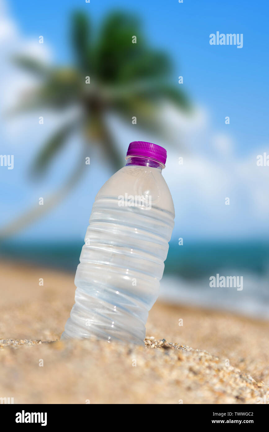 Bottle of cold fresh water on beach sand with palm background. Summer concept - Stock Image
