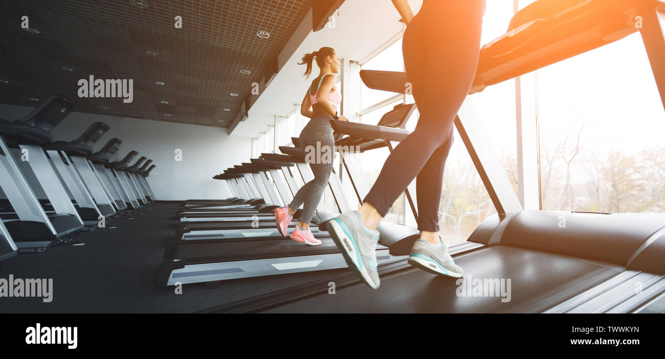 Running on treadmill. Girls working out in gym on sunny day - Stock Image