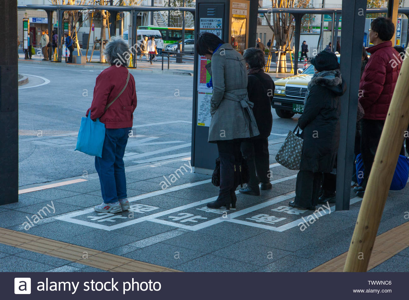 Tokyo, Japan - November 26, 2012: People stand in clear sign posted lines waiting for the bus at the stop. Everything well organised - Stock Image