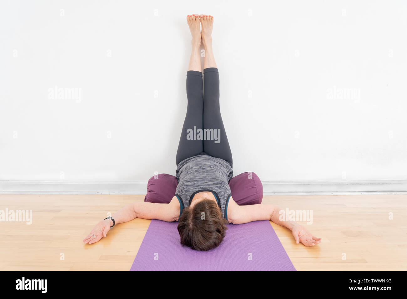a 47 year old female yoga instructor uses bolsters in a