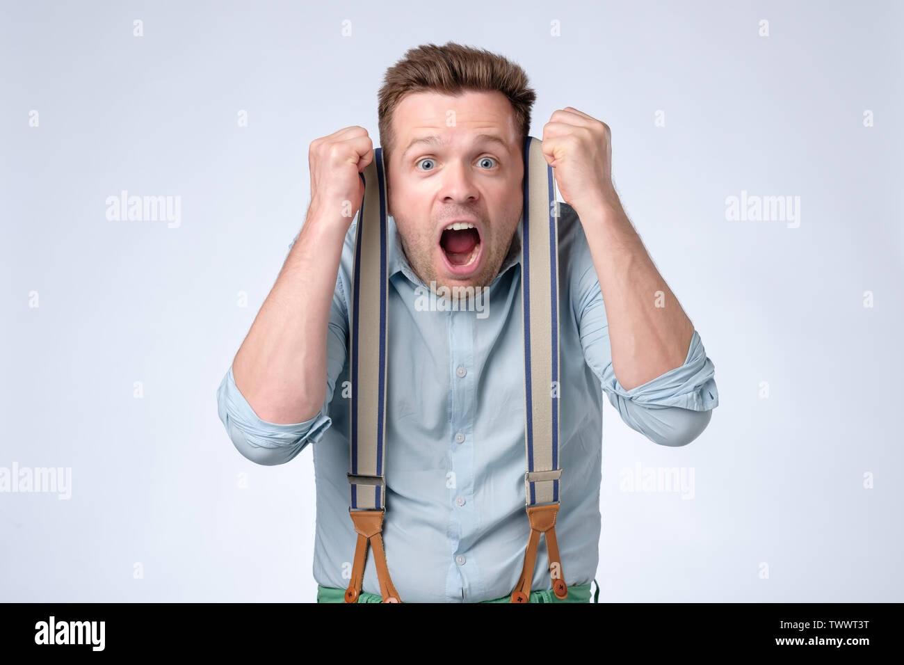 Shocked face of young european man in blue shirt and suspenders - Stock Image