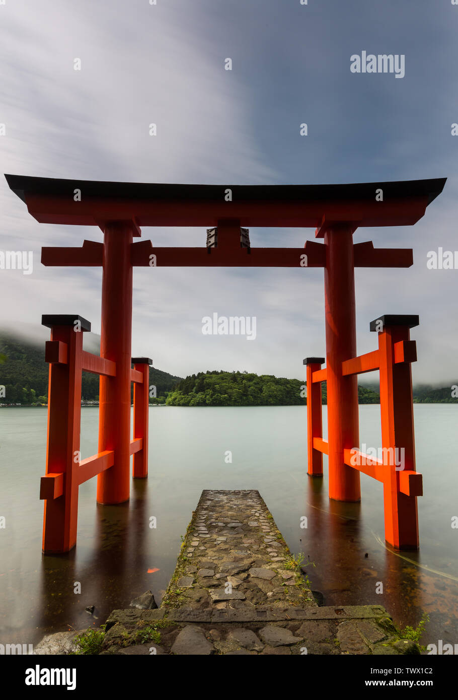 Hakone Shrine at lake Ashi in colorfull ornage during a long exposure with blurred couds in the wind. - Stock Image