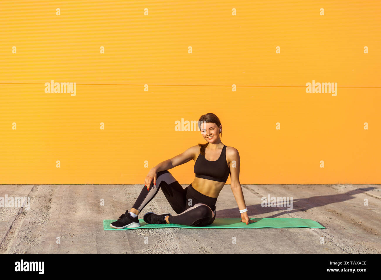 Young attractive woman wearing black sporwear practicing sport exercises in morning on street, sitting on green mat bands and rest after training, loo - Stock Image