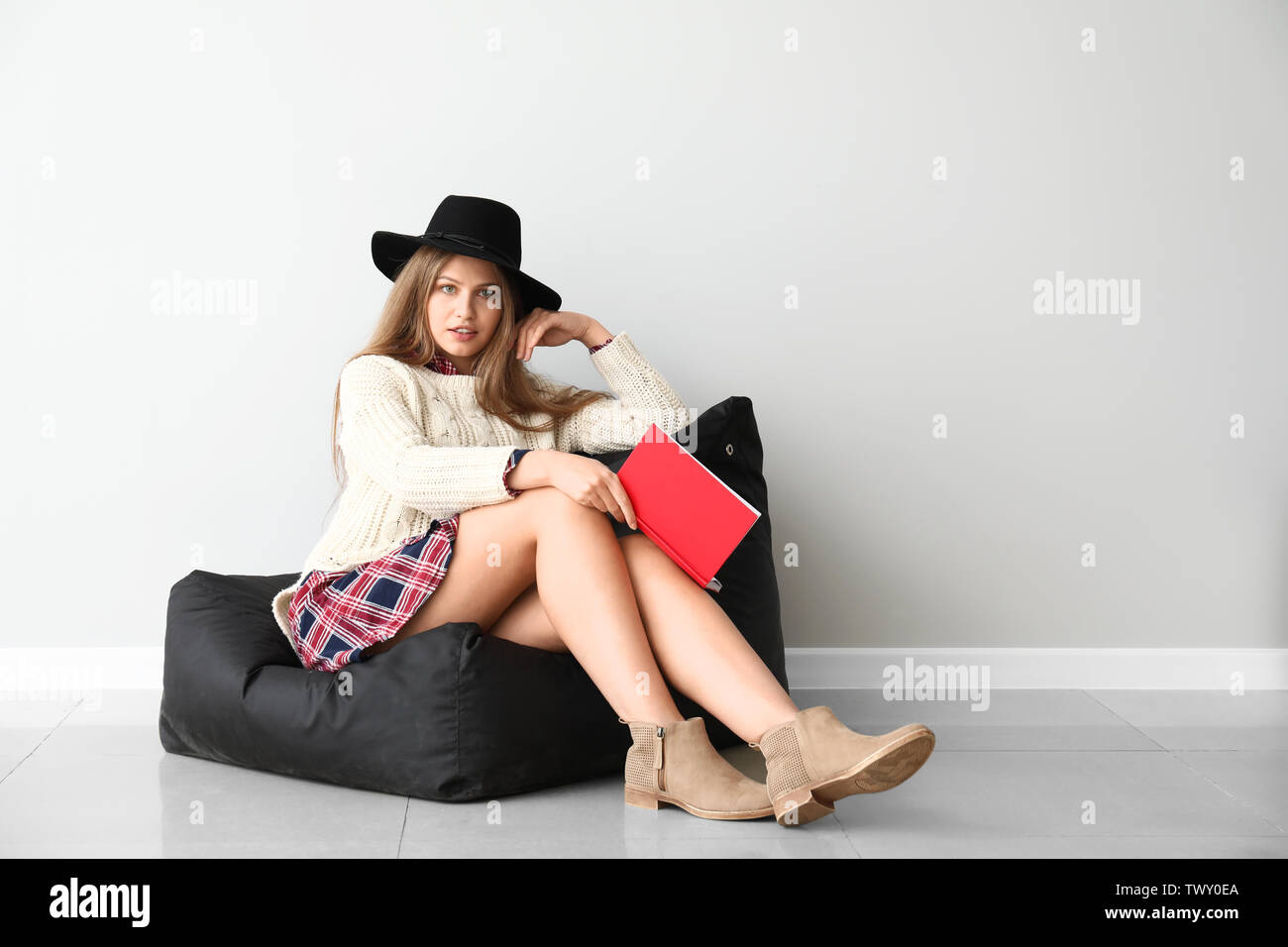 Beautiful young woman with book sitting near light wall - Stock Image