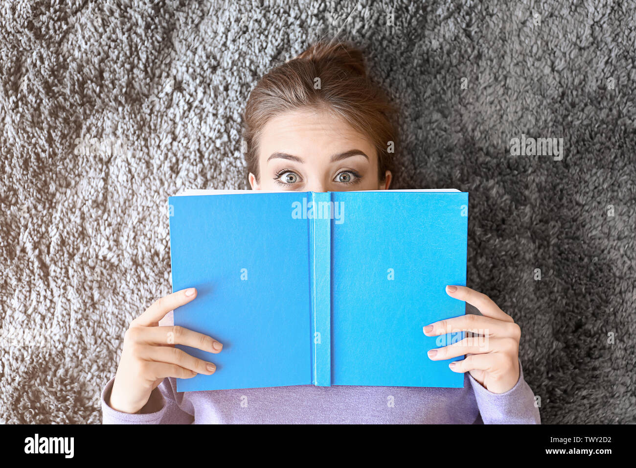 Surprised young woman with book lying on floor, top view - Stock Image
