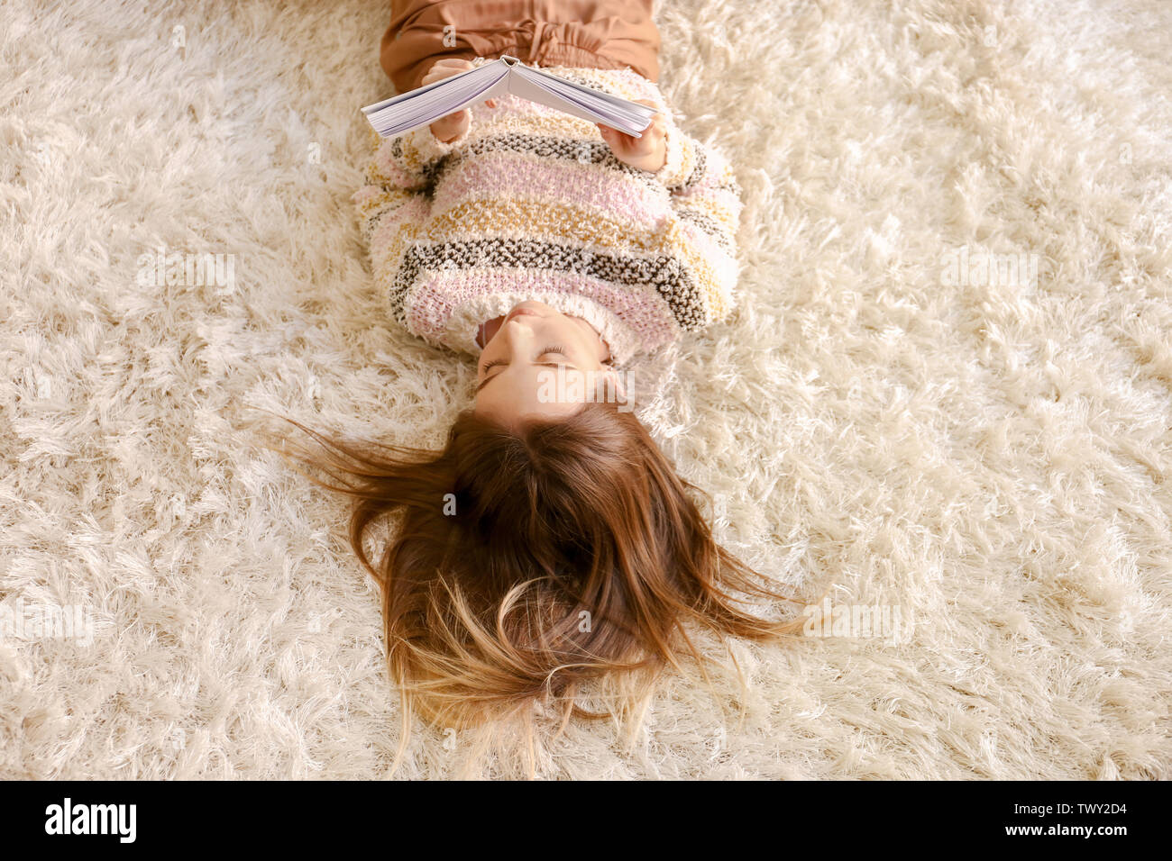 Beautiful young woman reading book while lying on floor at home - Stock Image
