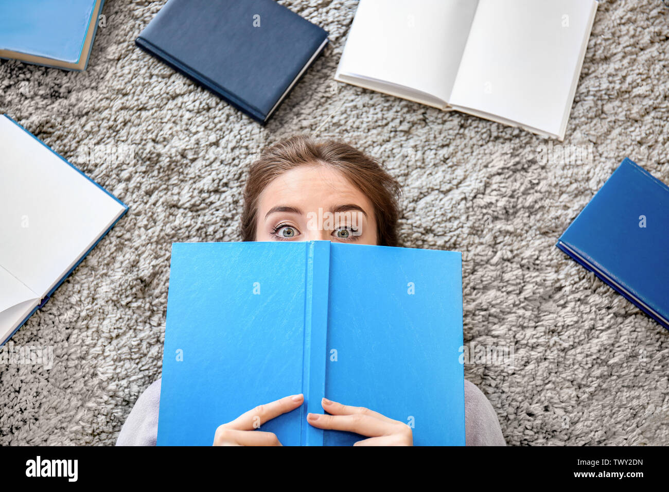 Female student reading books at home - Stock Image