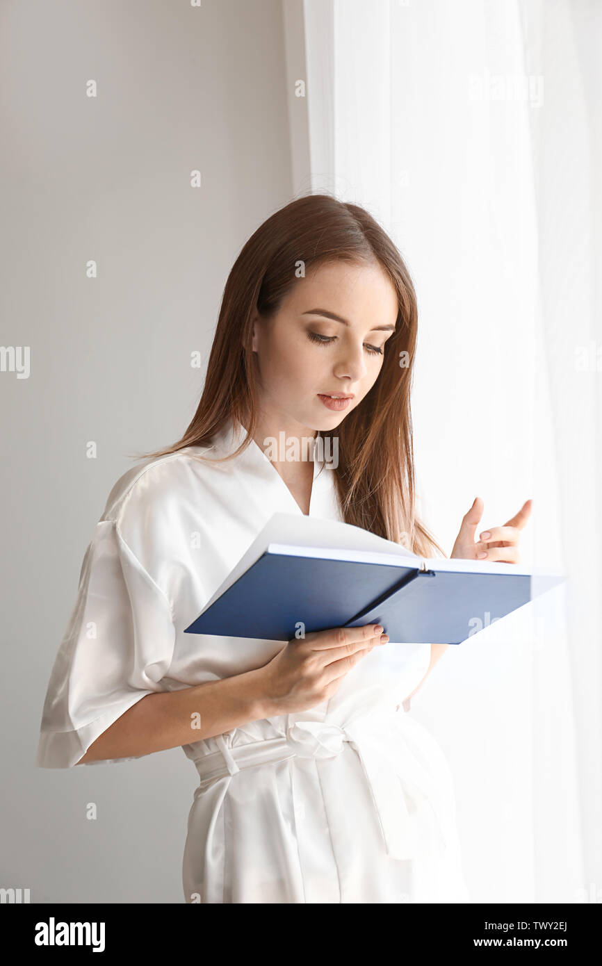 Beautiful young woman reading book near window - Stock Image