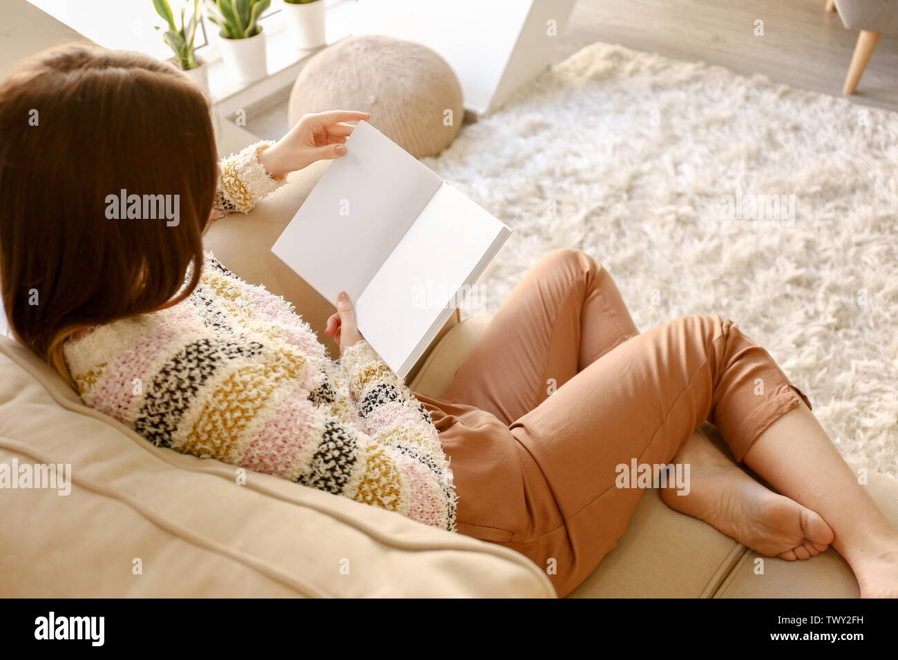 Beautiful young woman reading book at home - Stock Image