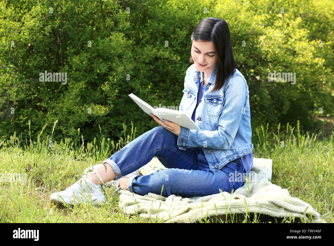 Beautiful young woman reading book in park - Stock Image