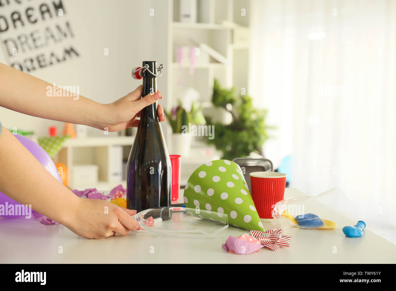 Female cleaner working in office after party - Stock Image