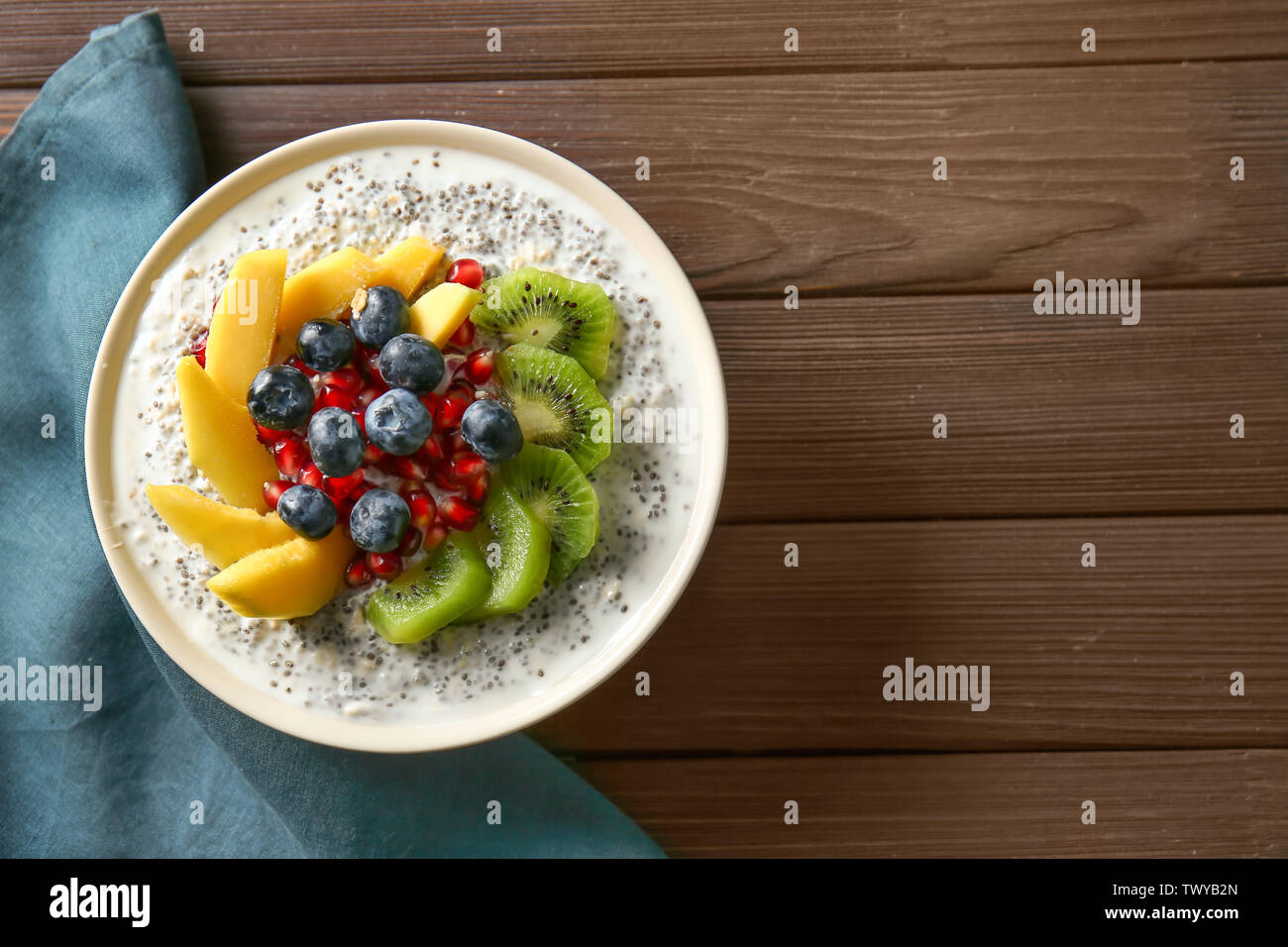 Bowl with tasty chia dessert on wooden table - Stock Image