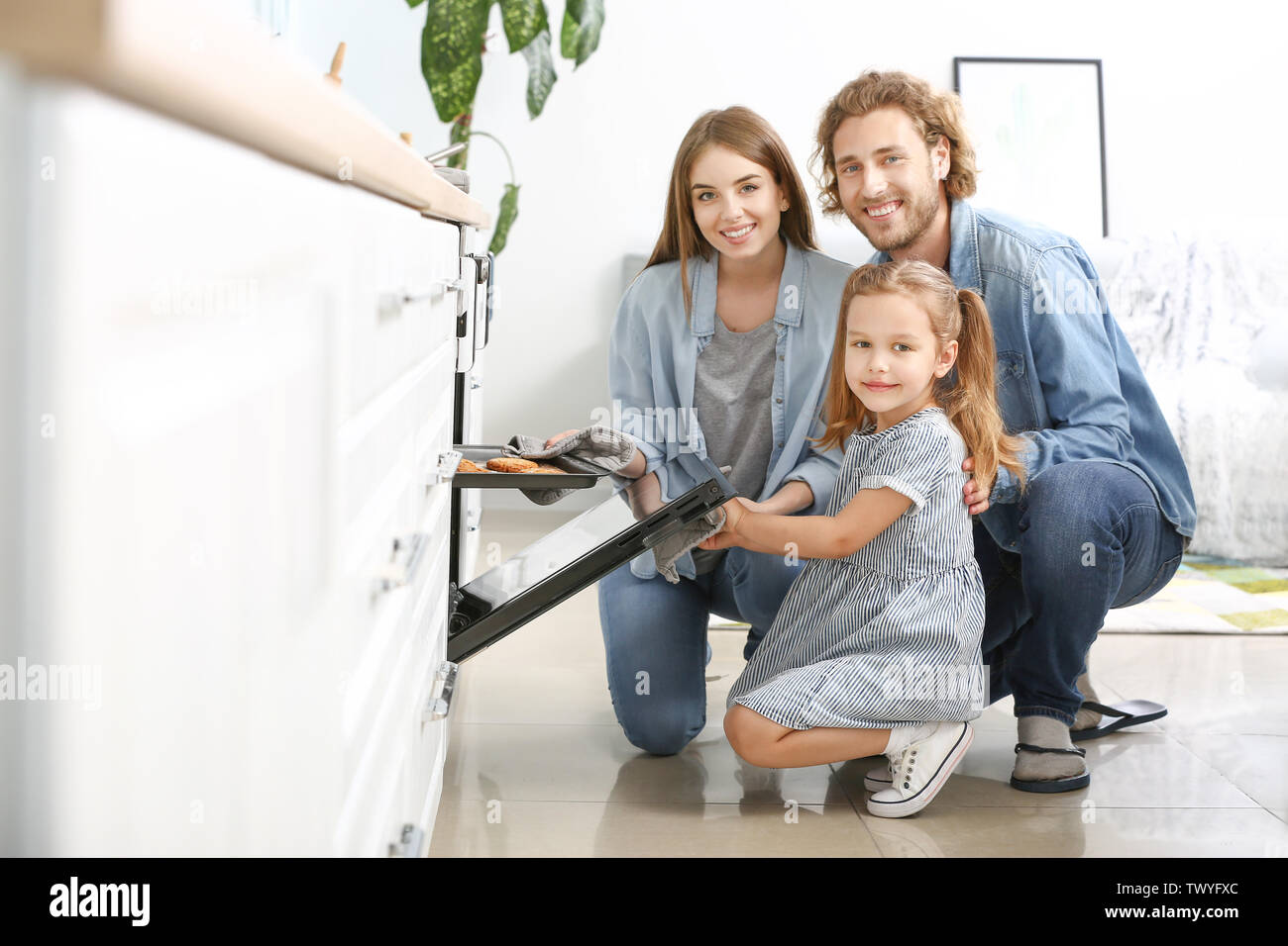 Happy family baking tasty cookies at home - Stock Image