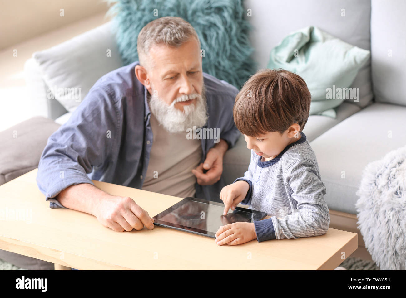 Cute little boy and his grandfather with tablet computer at home - Stock Image