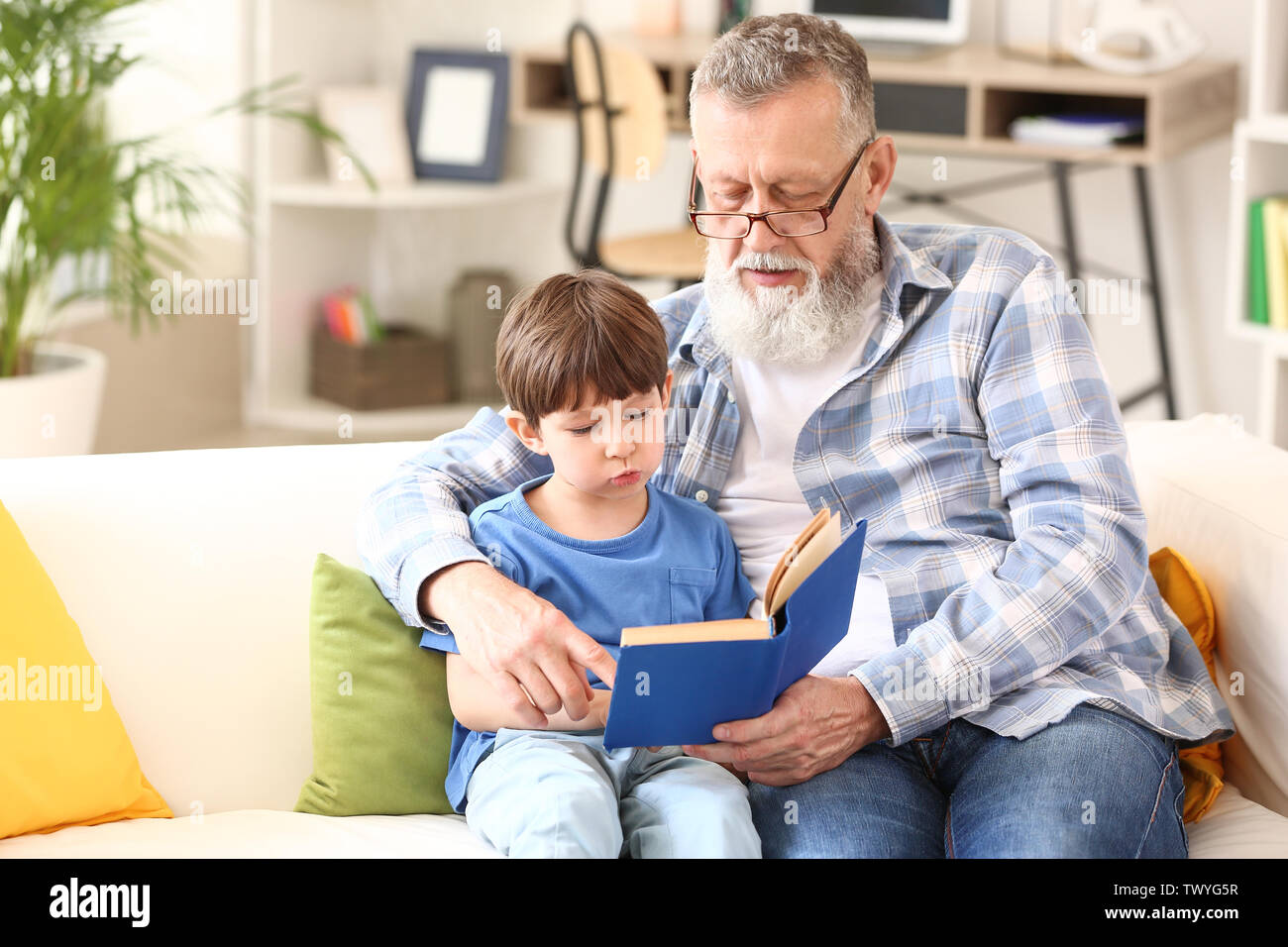 Cute little boy reading book with grandfather at home - Stock Image