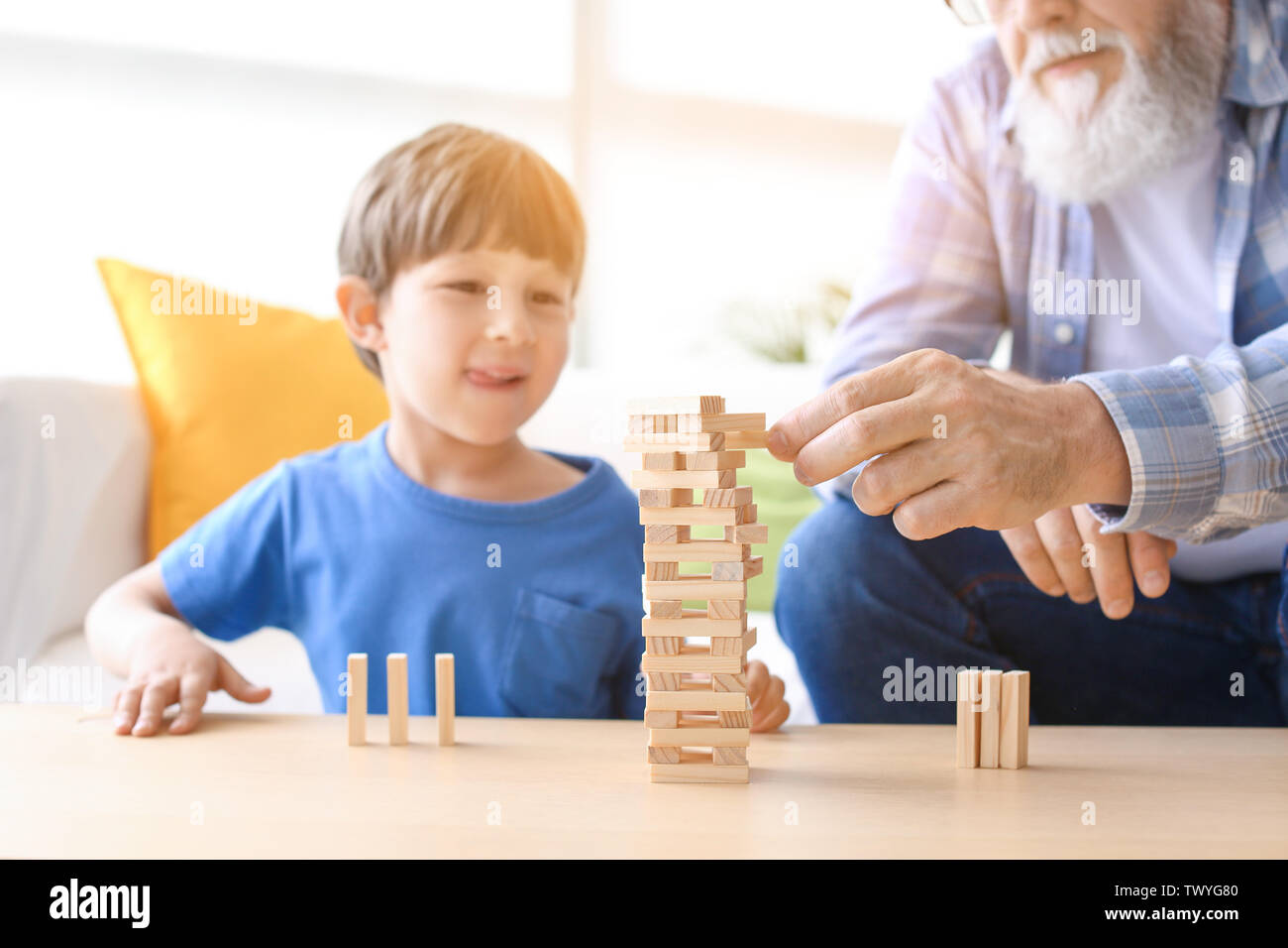 Cute little boy playing with grandfather at home - Stock Image