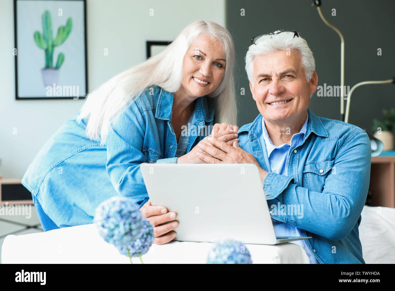 Portrait of happy mature couple with laptop at home - Stock Image