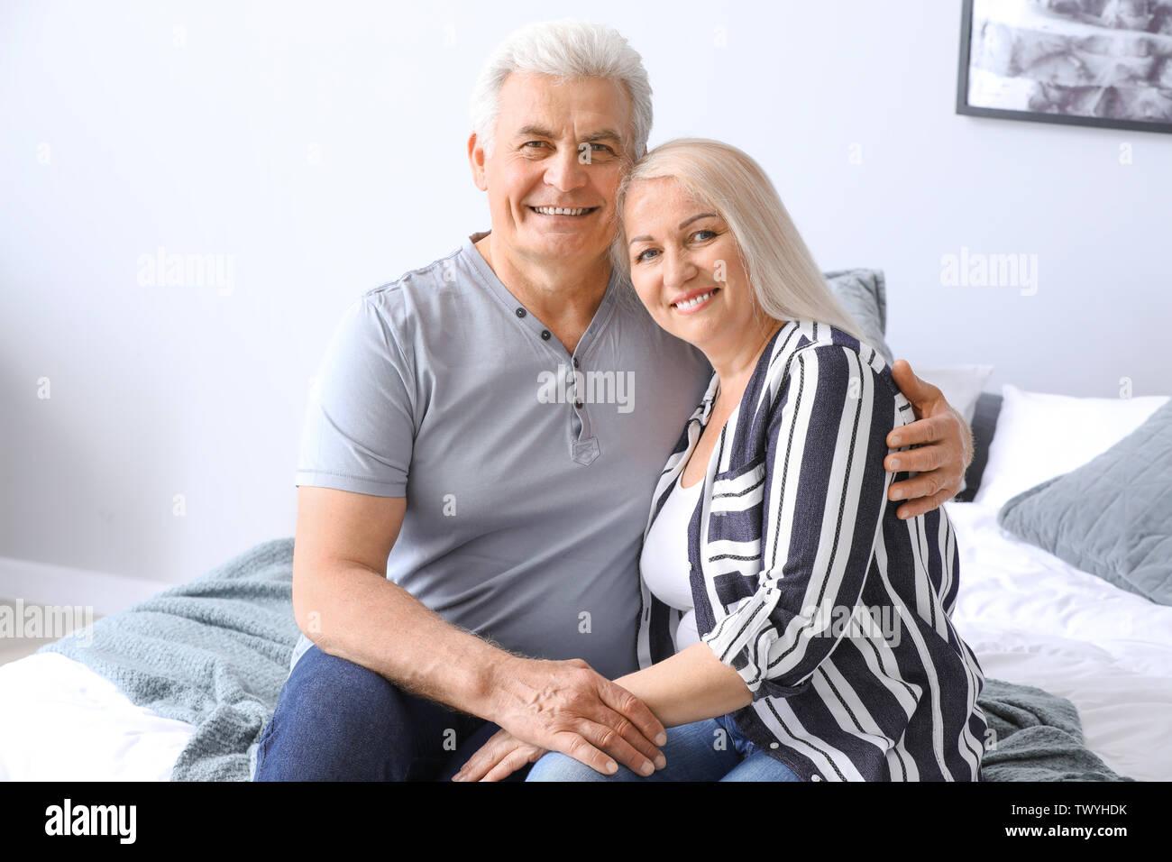 Portrait of happy mature couple in bedroom - Stock Image