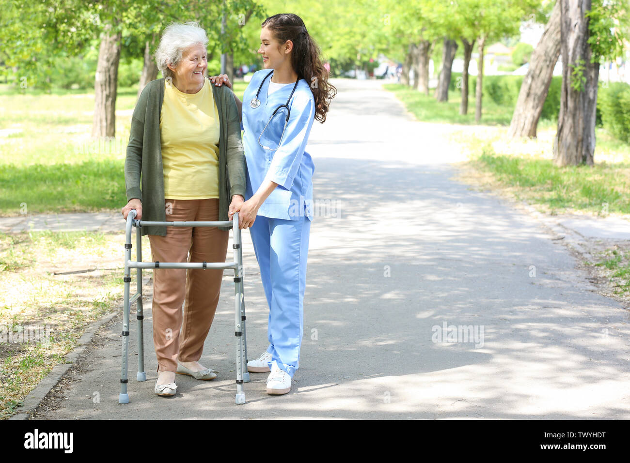 Caregiver walking with senior woman in park - Stock Image