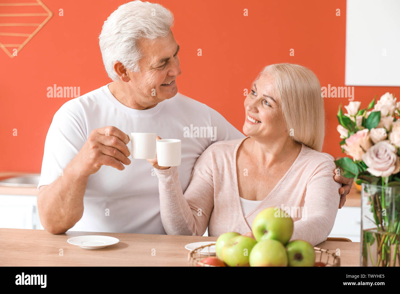 Portrait of happy mature couple drinking tea at home - Stock Image