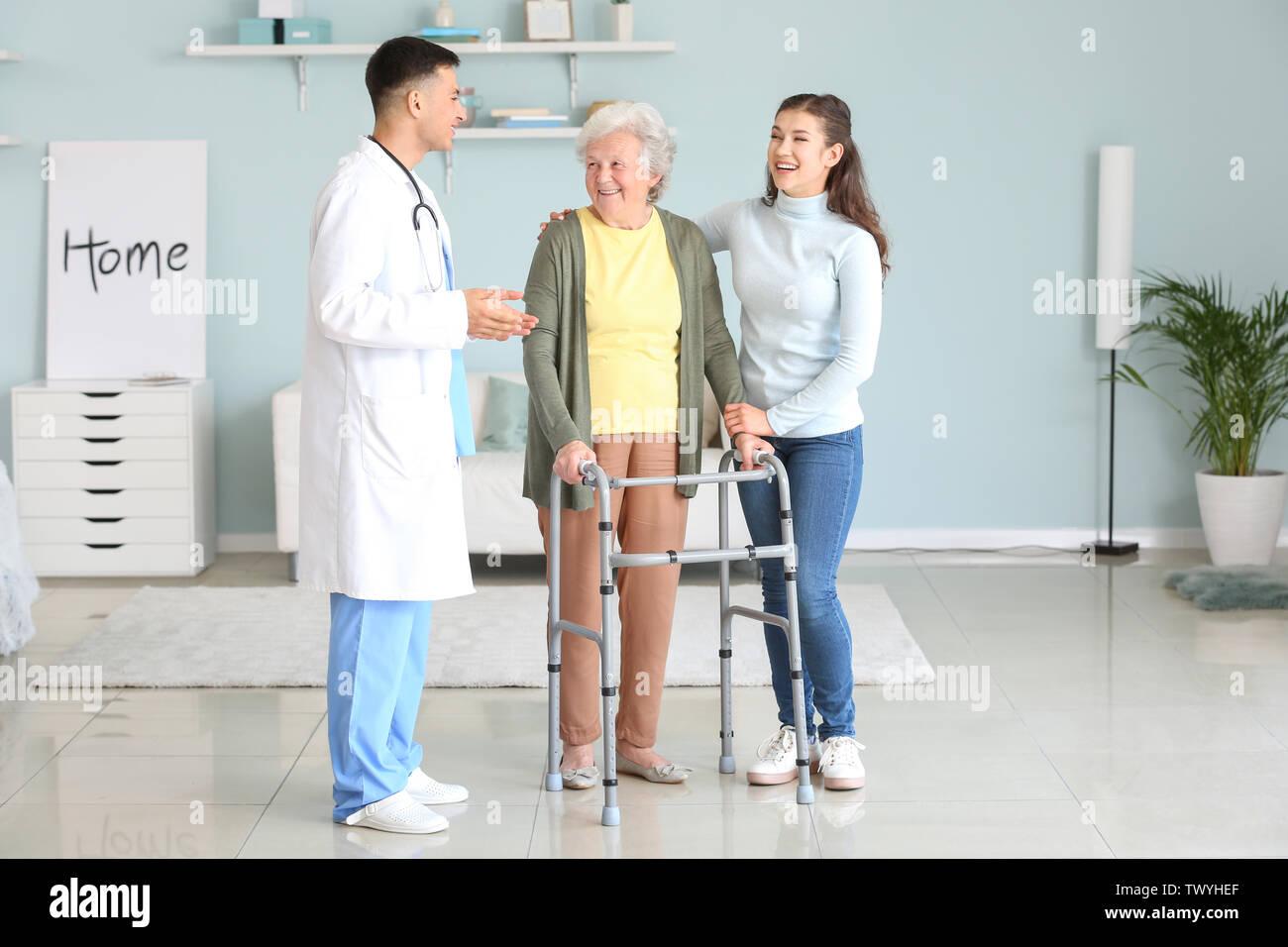 Doctor visiting senior woman at home - Stock Image