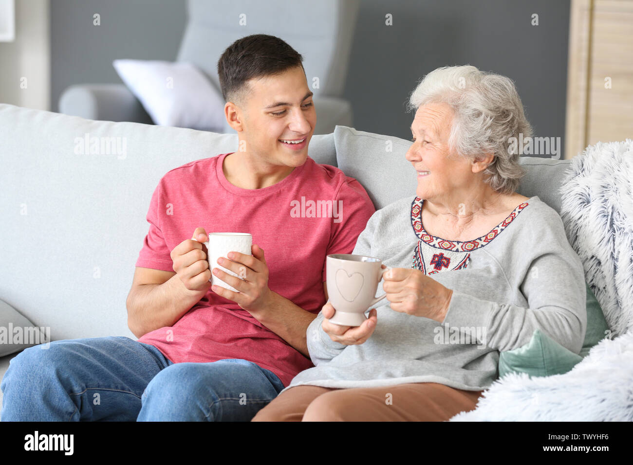 Senior woman with her grandson resting at home - Stock Image