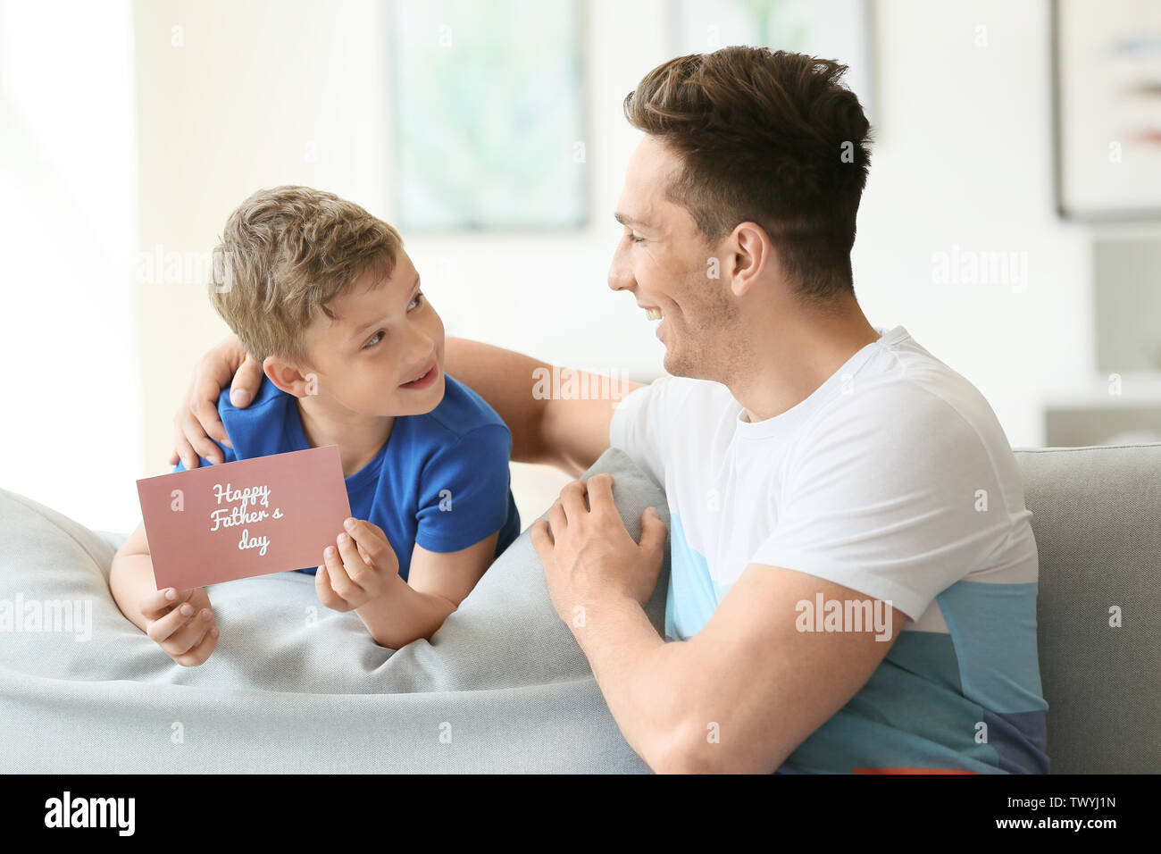 Little boy greeting his dad with Father's Day at home - Stock Image