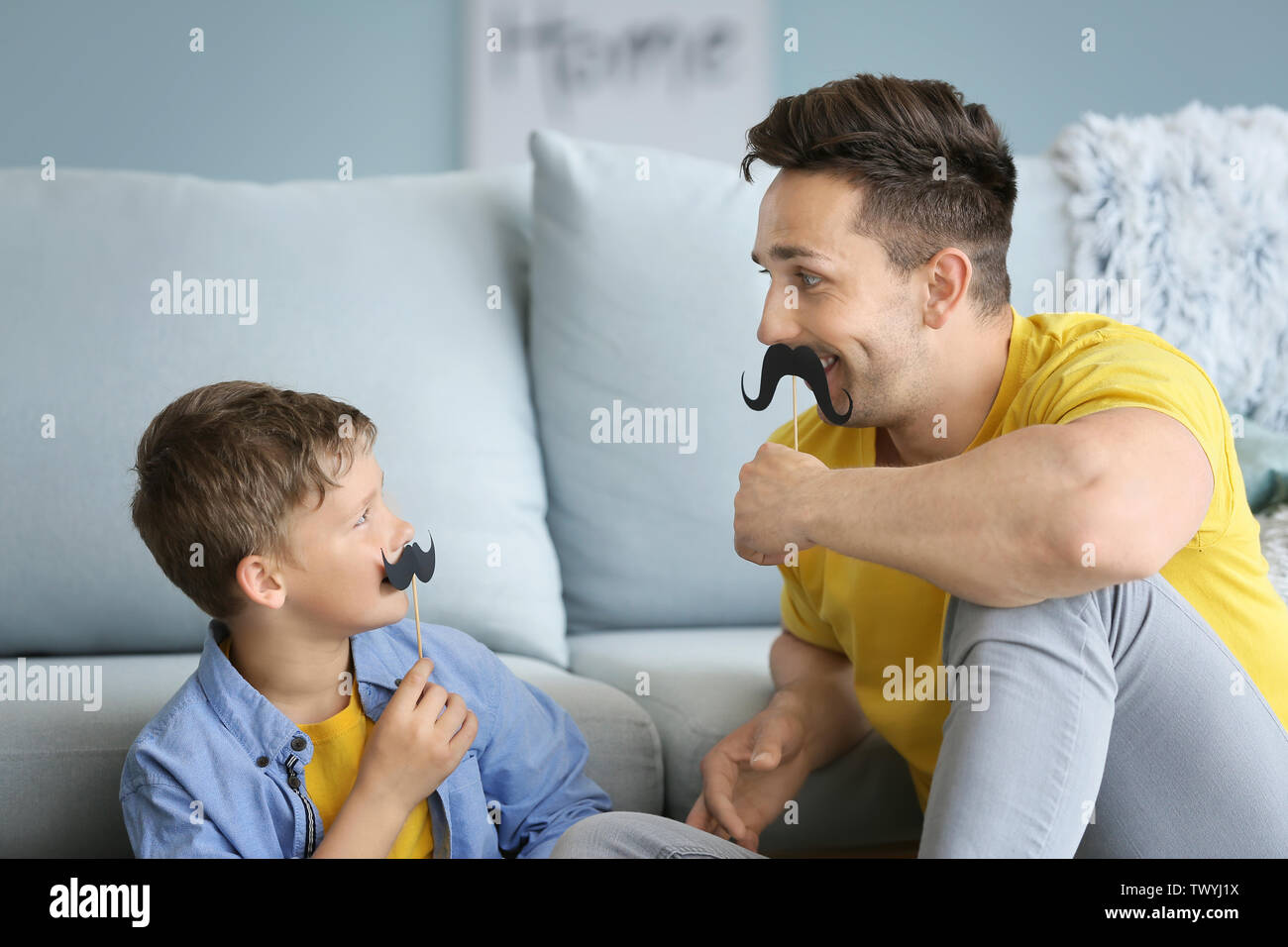 Portrait of funny father and son with fake mustache at home - Stock Image