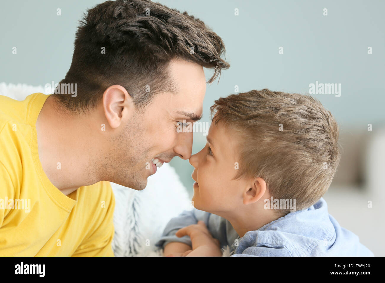 Portrait of happy father and son at home - Stock Image