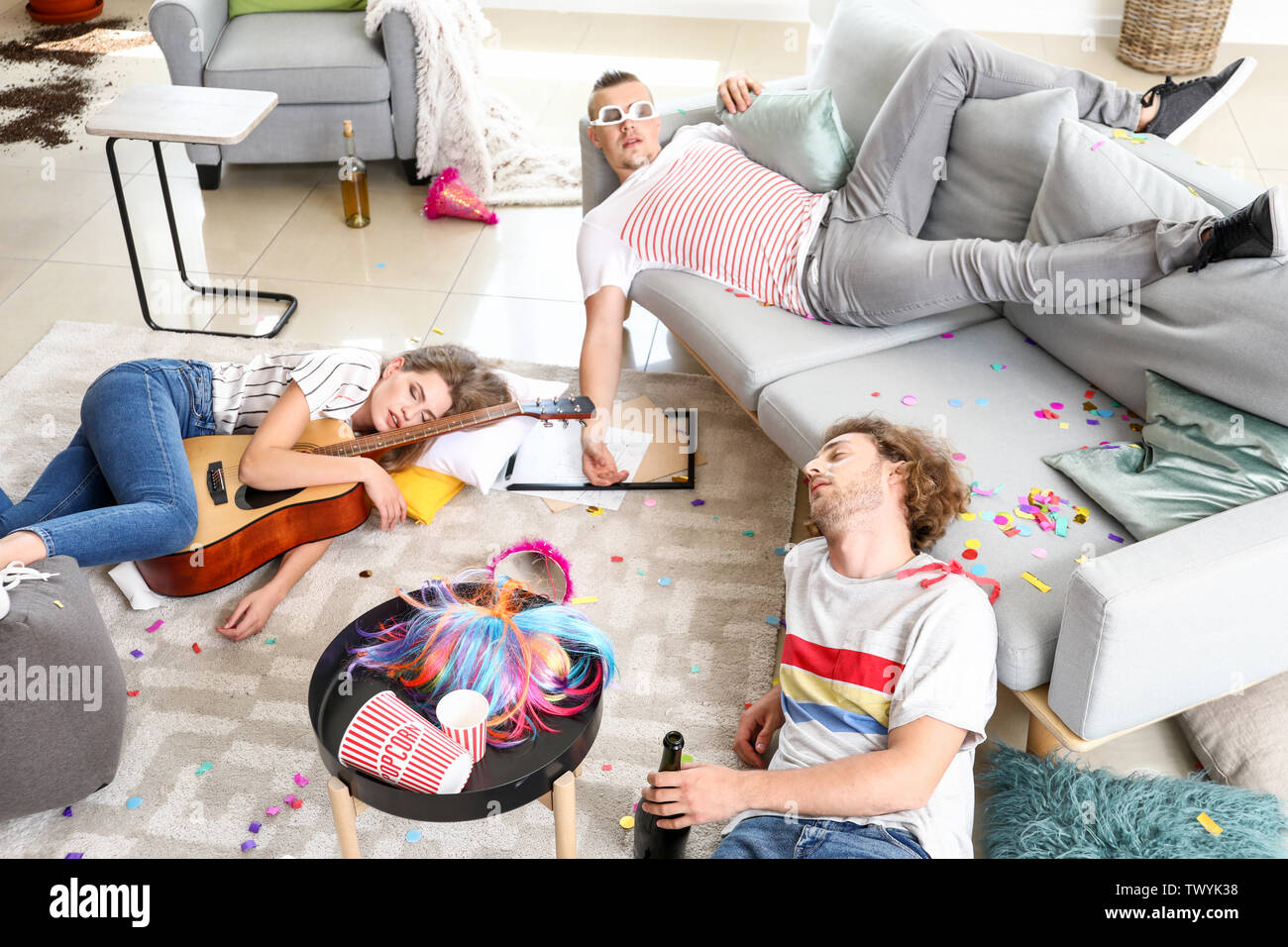 Young people sleeping after party at home - Stock Image