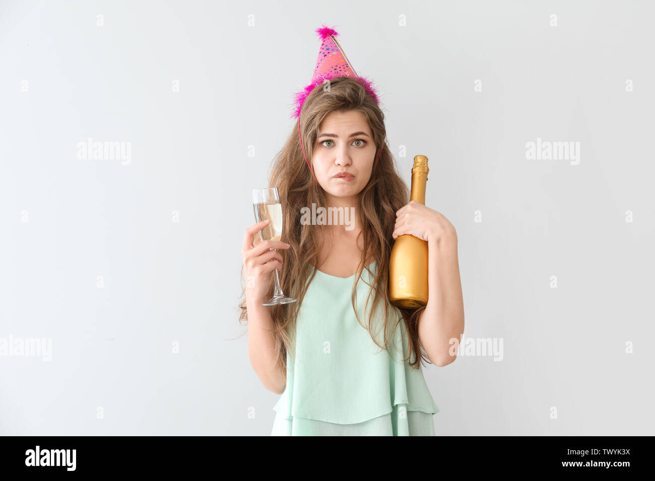 Drunk woman with party hat and champagne on light background - Stock Image