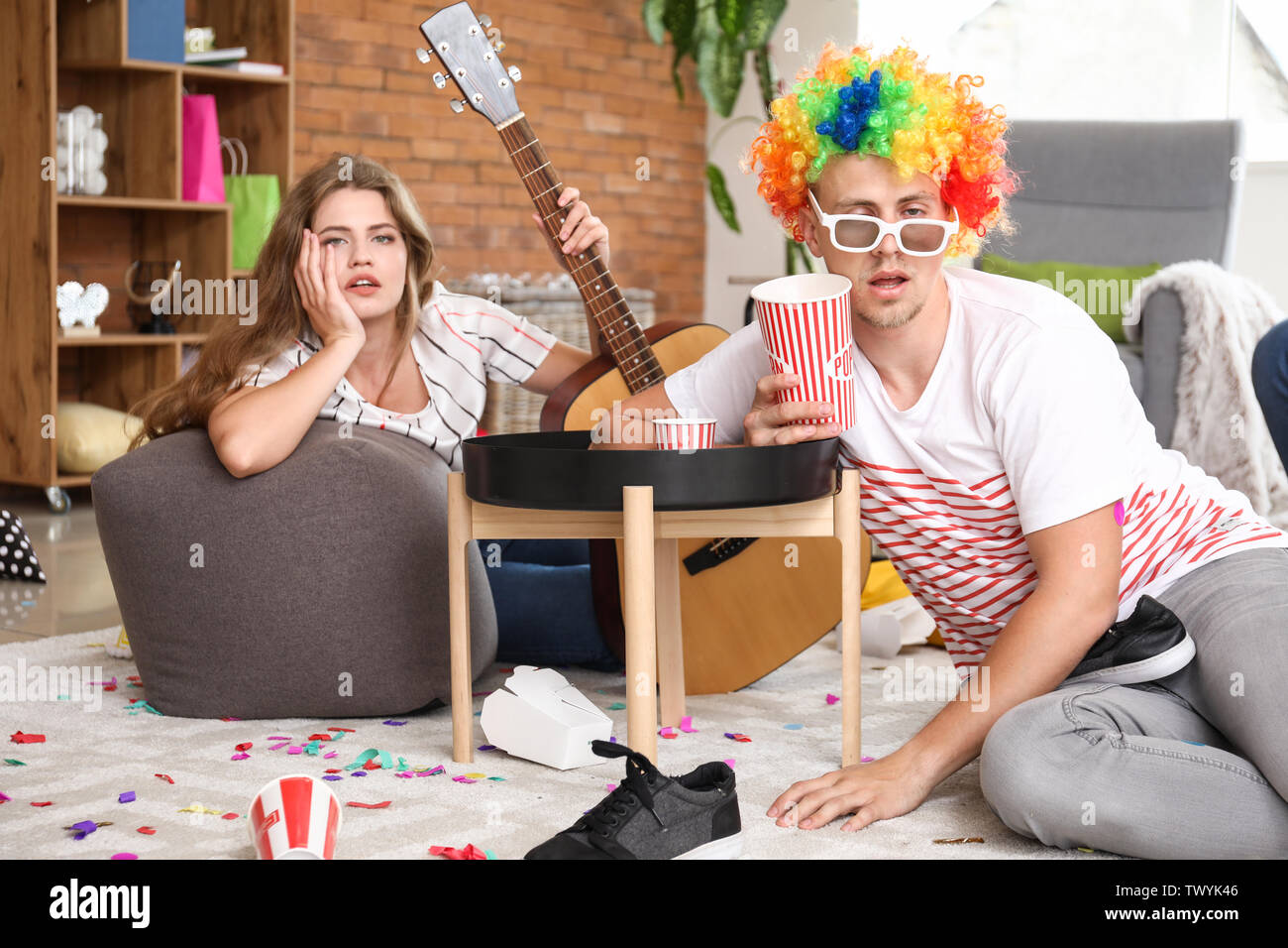 Young people with hangover after party at home - Stock Image
