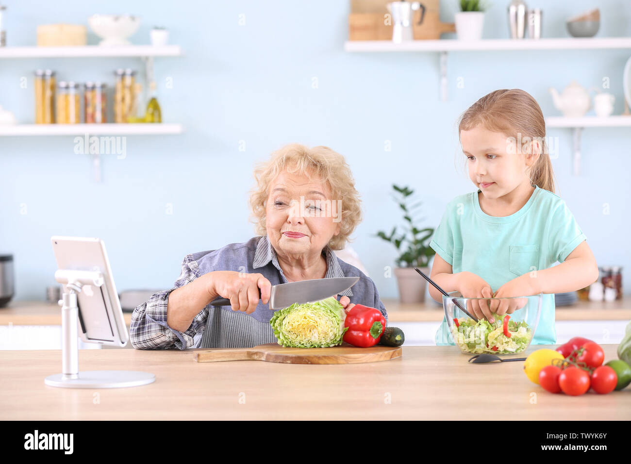 Cute little girl with grandmother preparing vegetable salad in kitchen - Stock Image