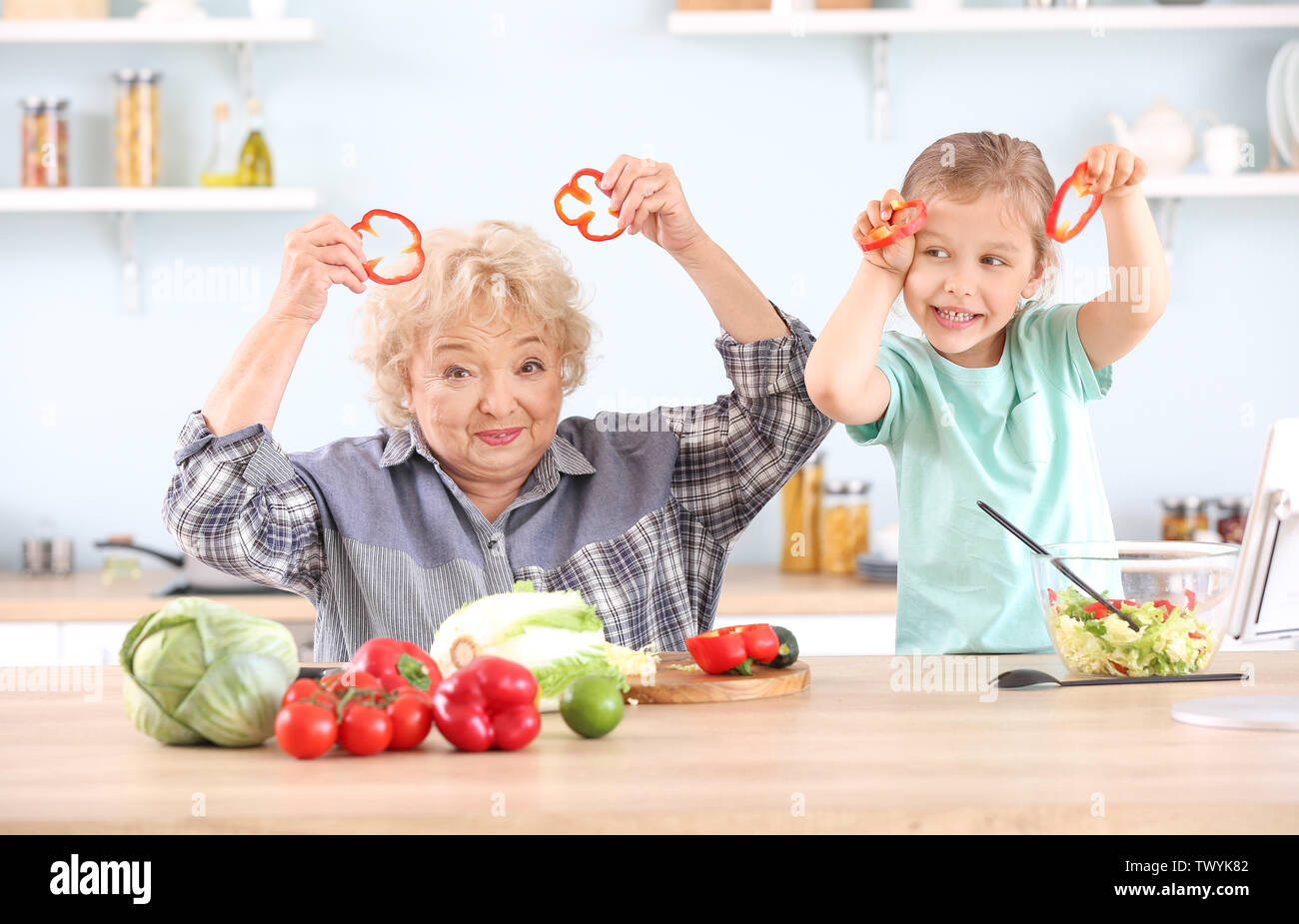 Cute little girl with grandmother having fun in kitchen - Stock Image