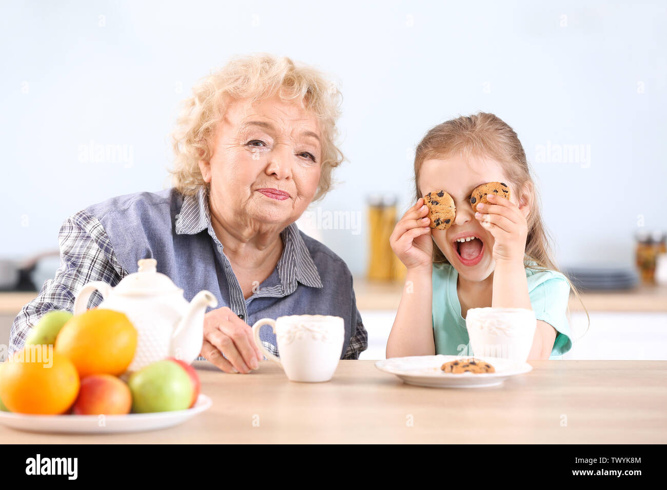 Cute little girl and grandmother drinking tea with cookies in kitchen - Stock Image