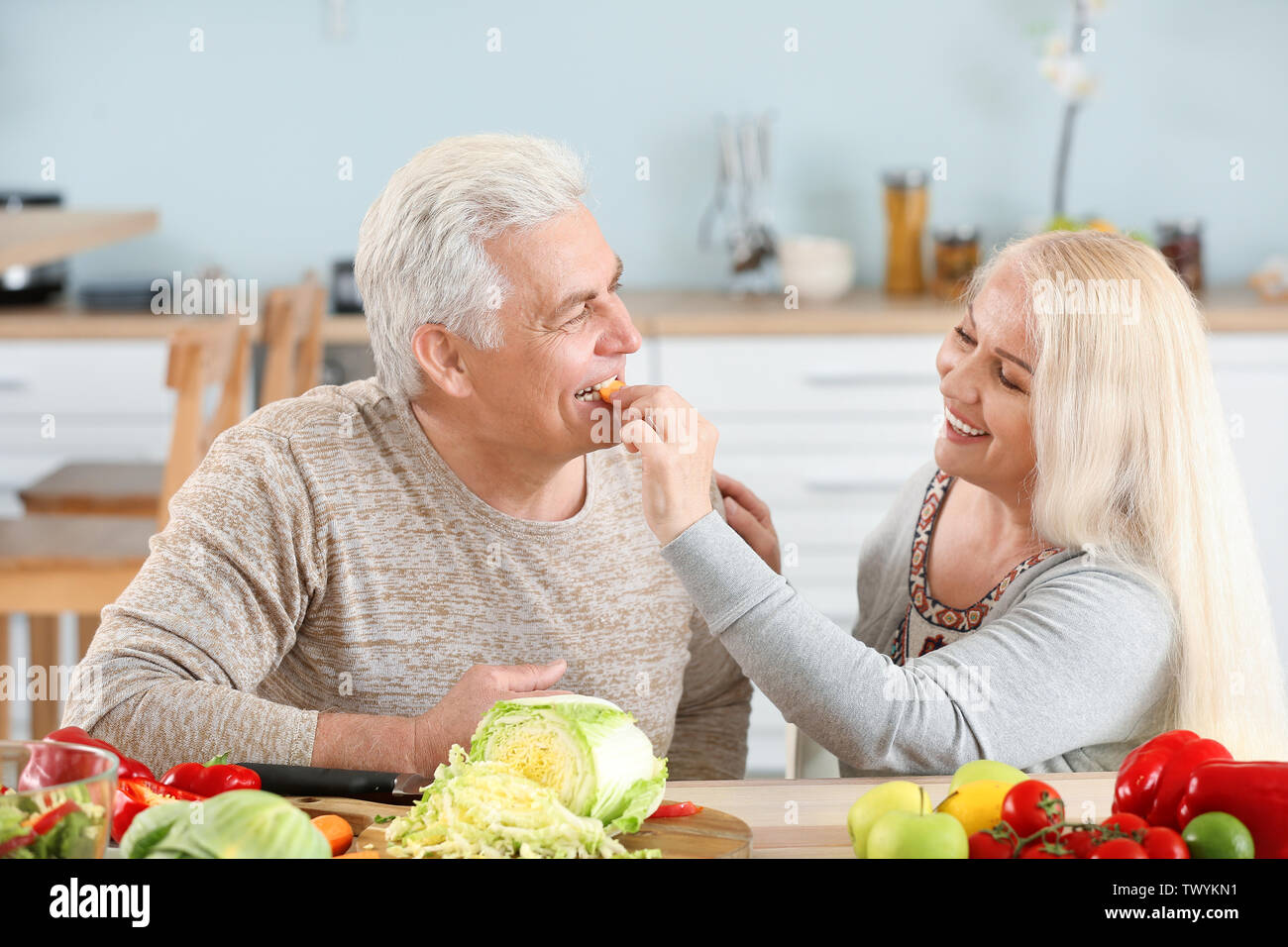 Mature woman feeding her husband in kitchen - Stock Image