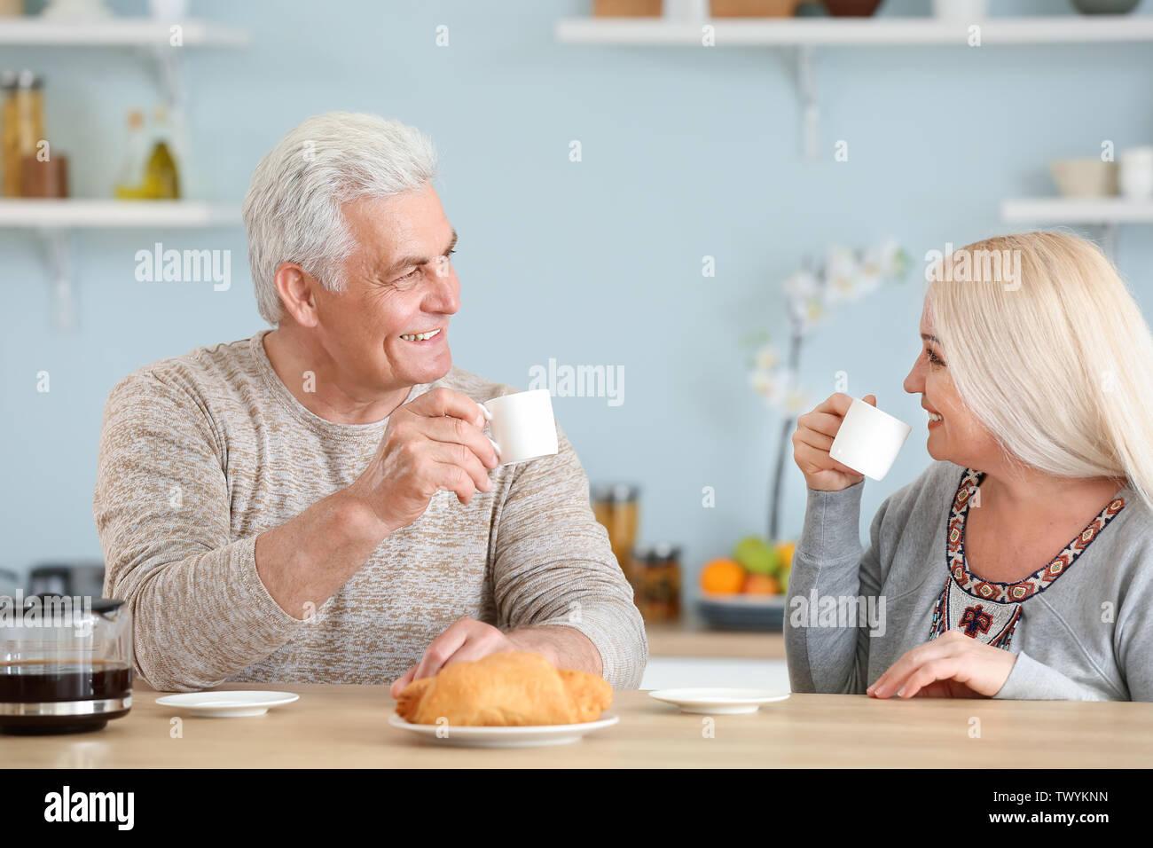 Portrait of happy mature couple having breakfast in kitchen - Stock Image