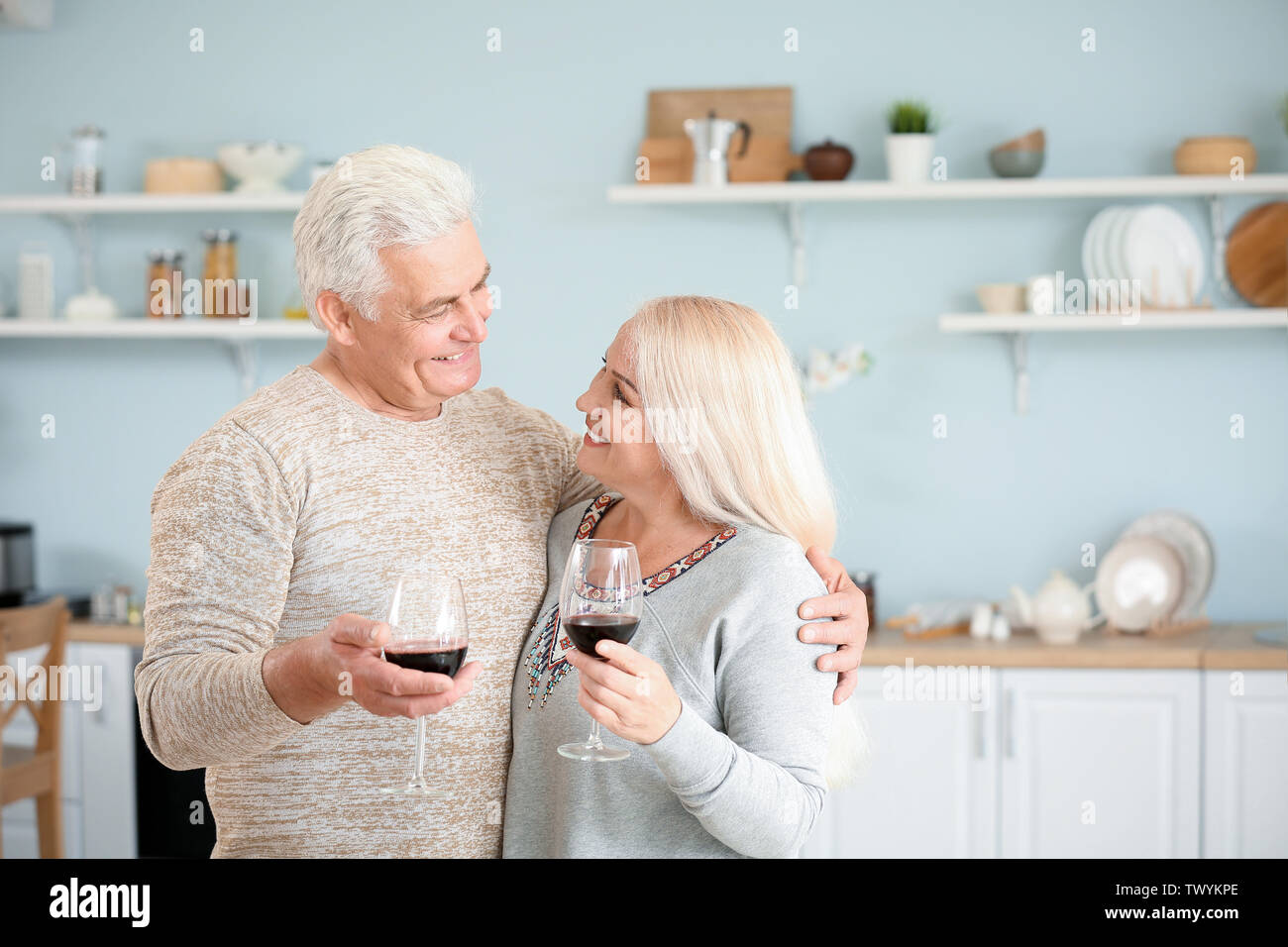 Happy mature couple drinking wine in kitchen - Stock Image