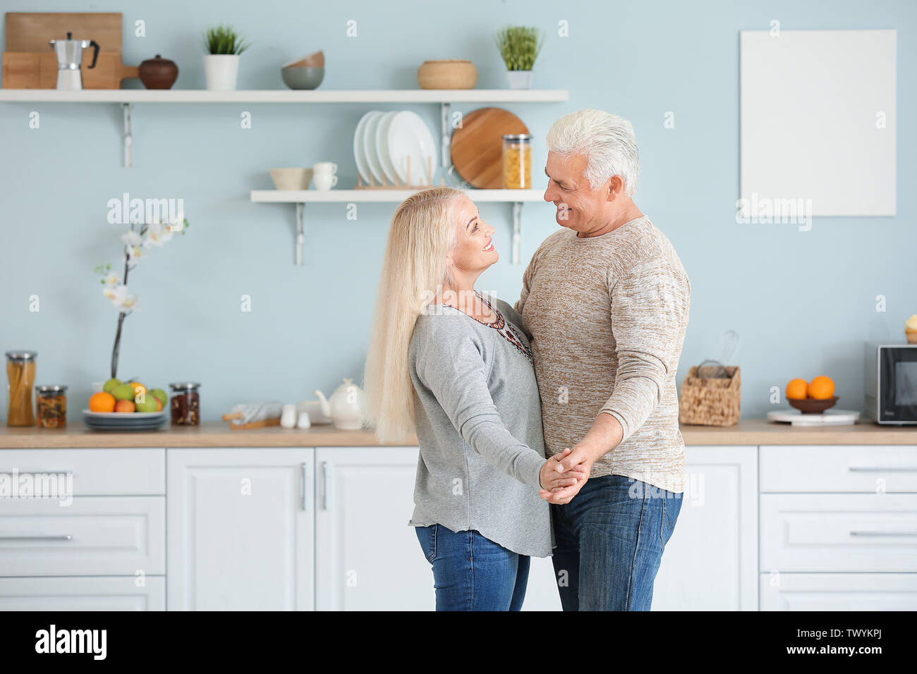 Portrait of happy mature couple dancing in kitchen - Stock Image
