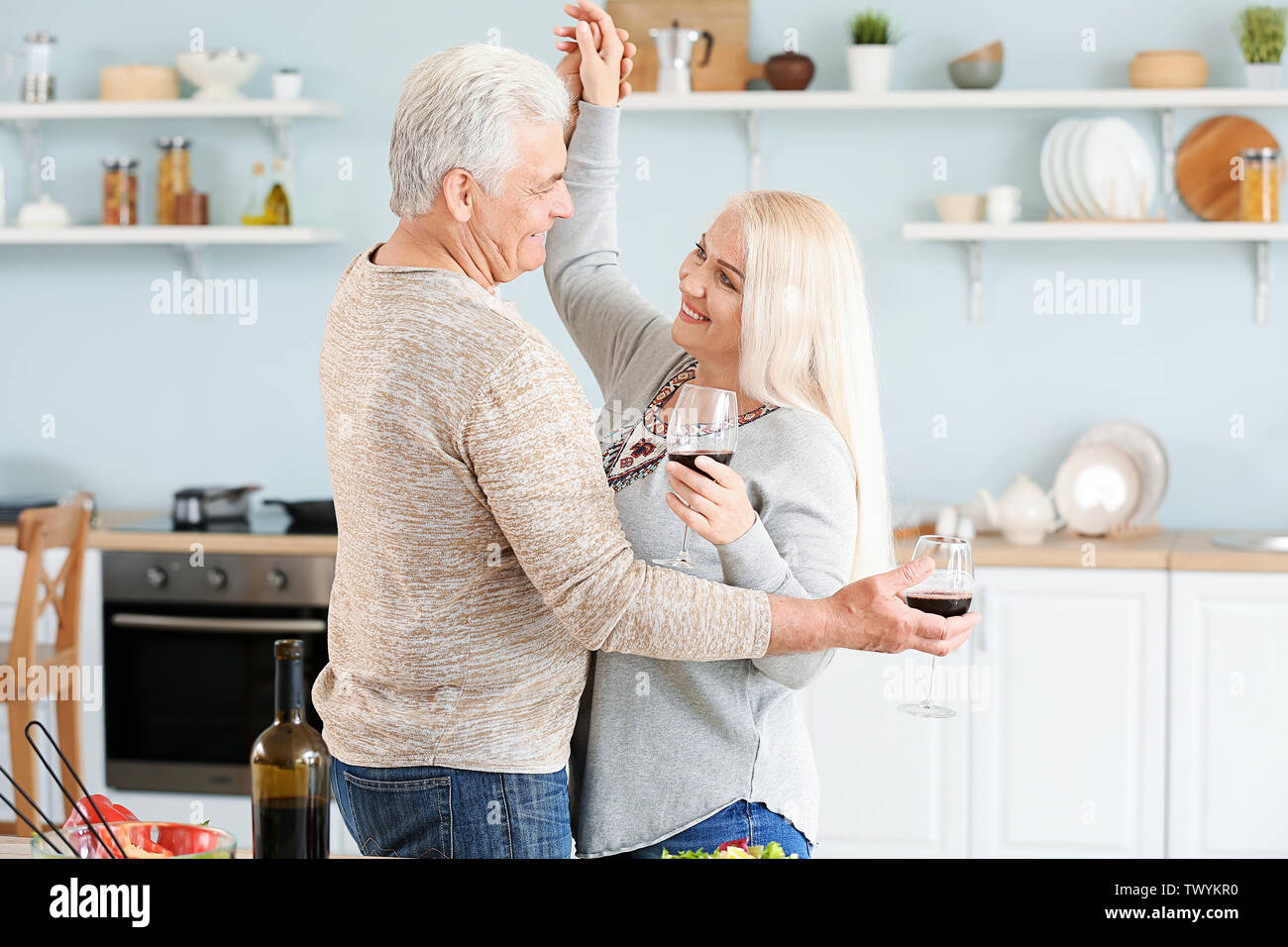 Portrait of happy mature couple dancing and drinking wine in kitchen - Stock Image