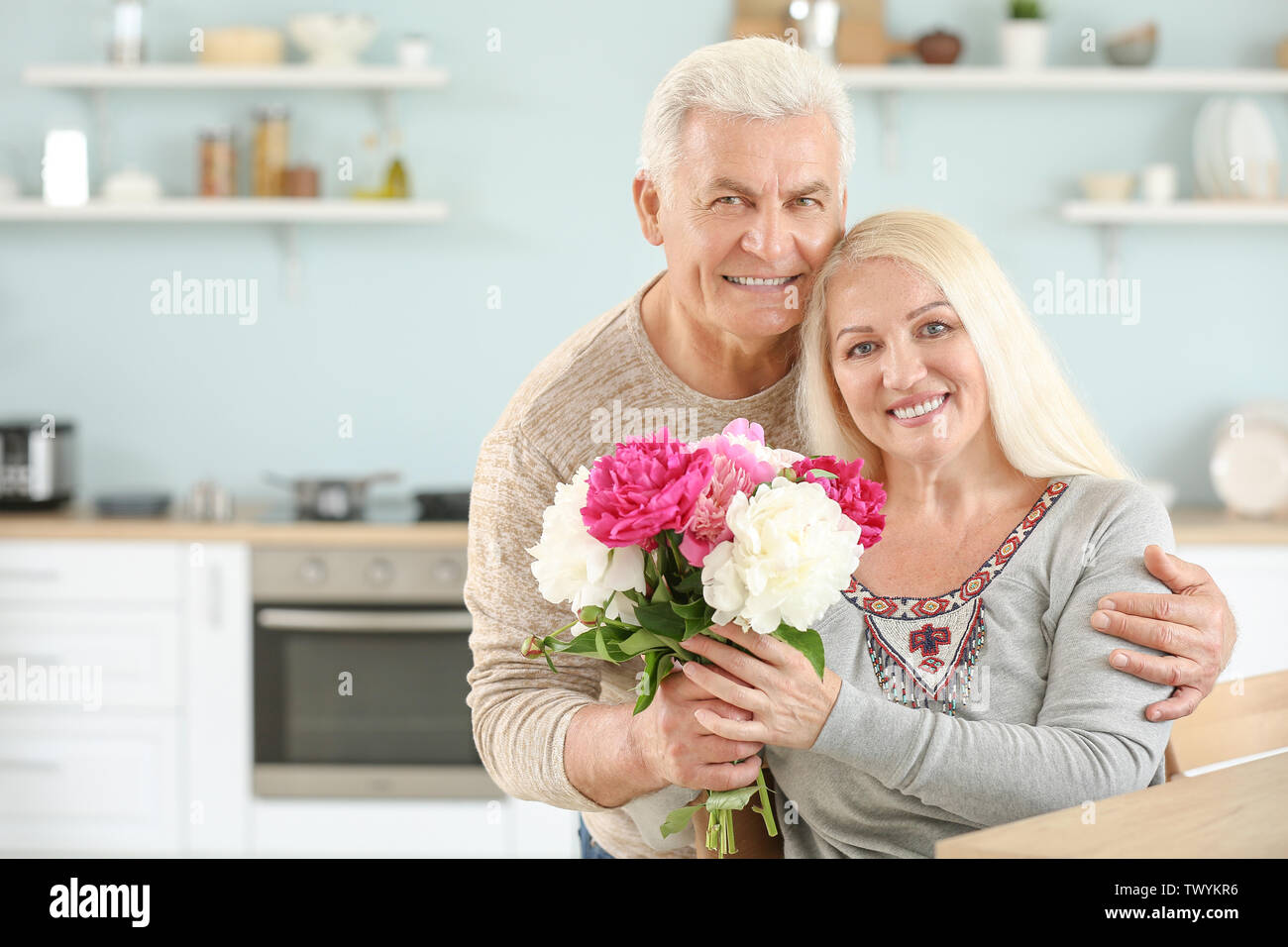 Portrait of happy mature couple with flowers in kitchen - Stock Image