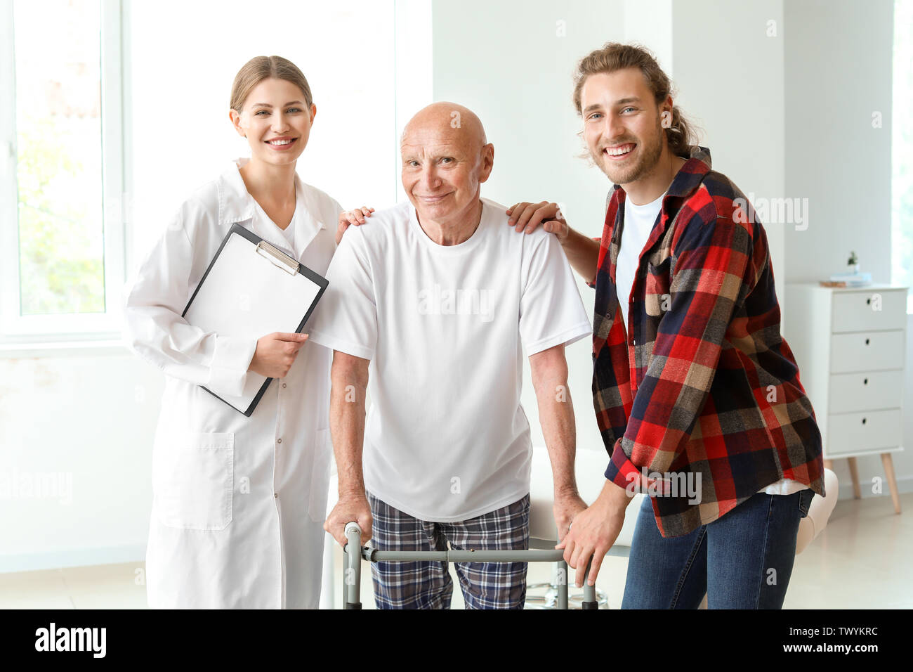 Young man visiting his elderly father in modern clinic - Stock Image