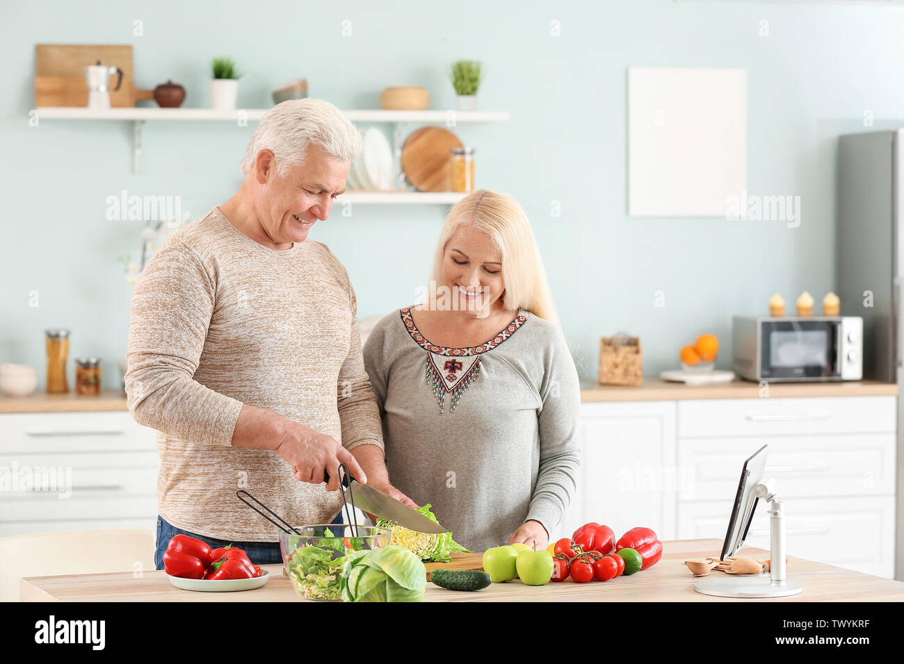 Portrait of happy mature couple cooking in kitchen - Stock Image