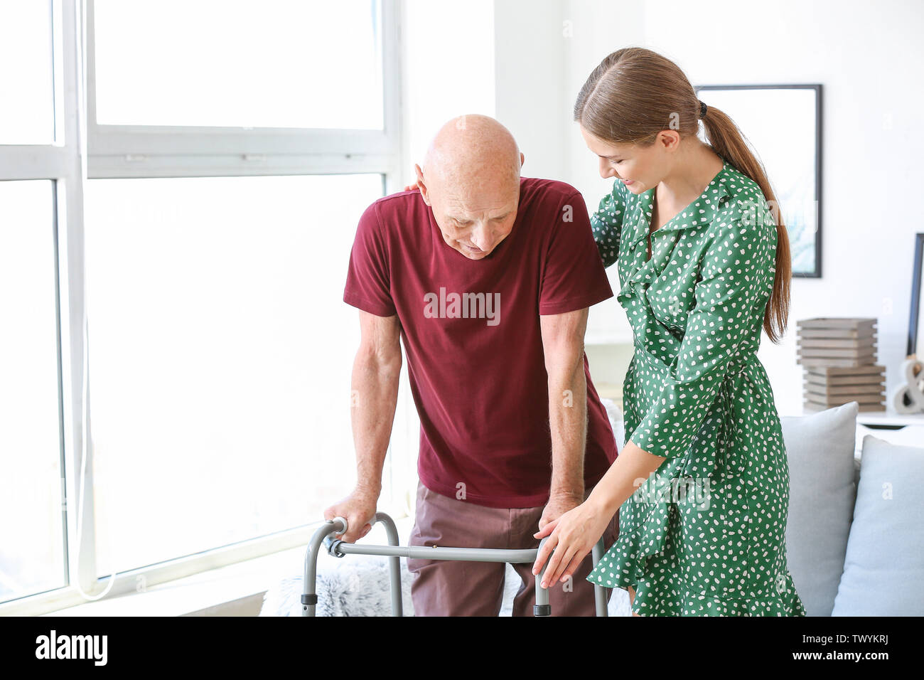 Young woman visiting her elderly father in nursing home - Stock Image