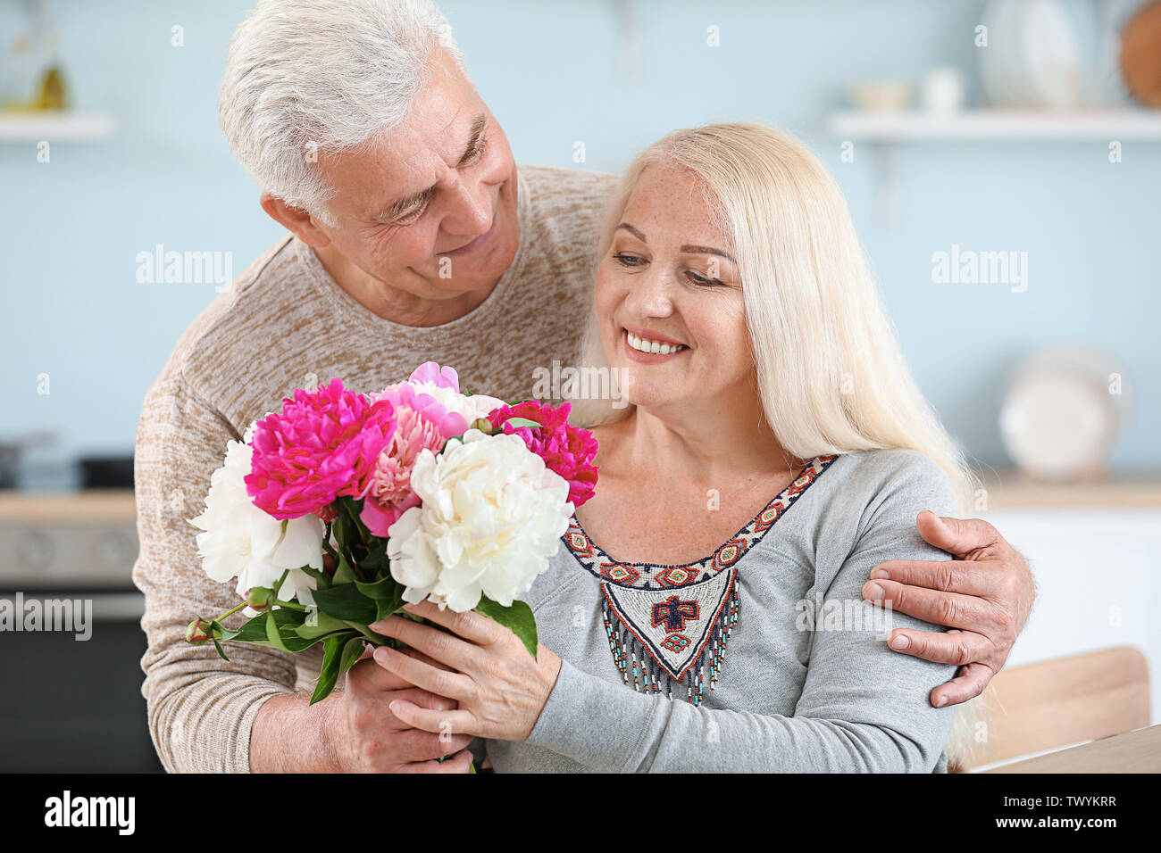 Mature man giving flowers to his wife in kitchen - Stock Image