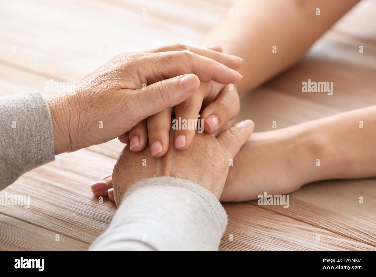 Hands of elderly woman and her granddaughter, closeup. Concept of care and support - Stock Image