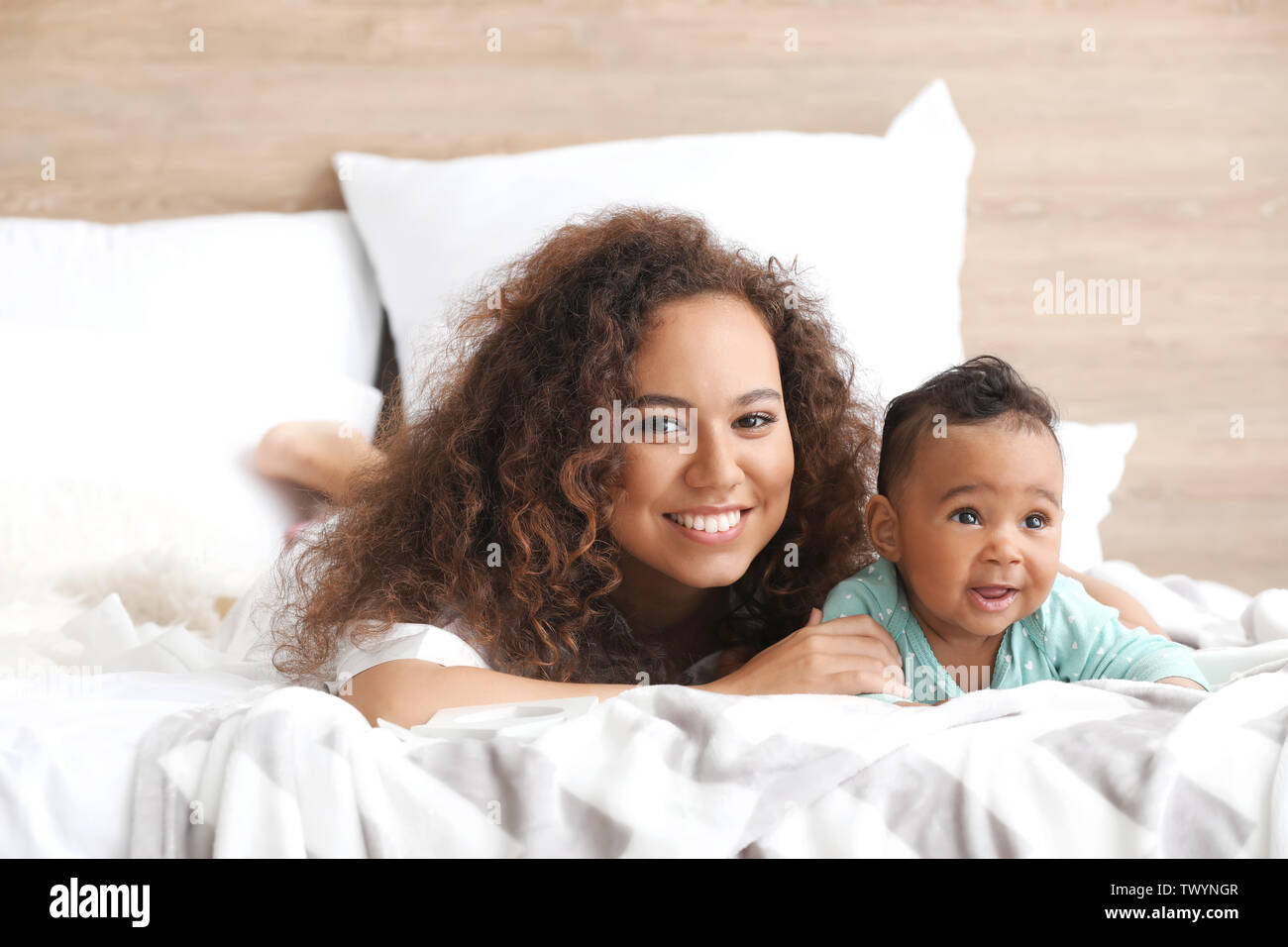 Happy African-American mother with cute little baby in bedroom - Stock Image
