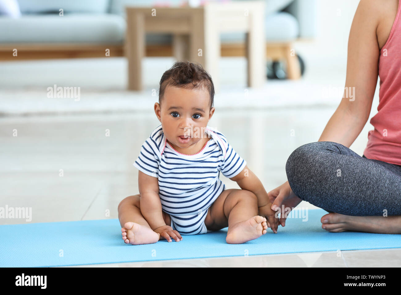 Little African-American boy and his sporty mother at home - Stock Image