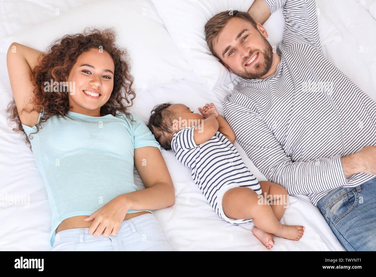 Portrait of happy interracial family in bedroom - Stock Image