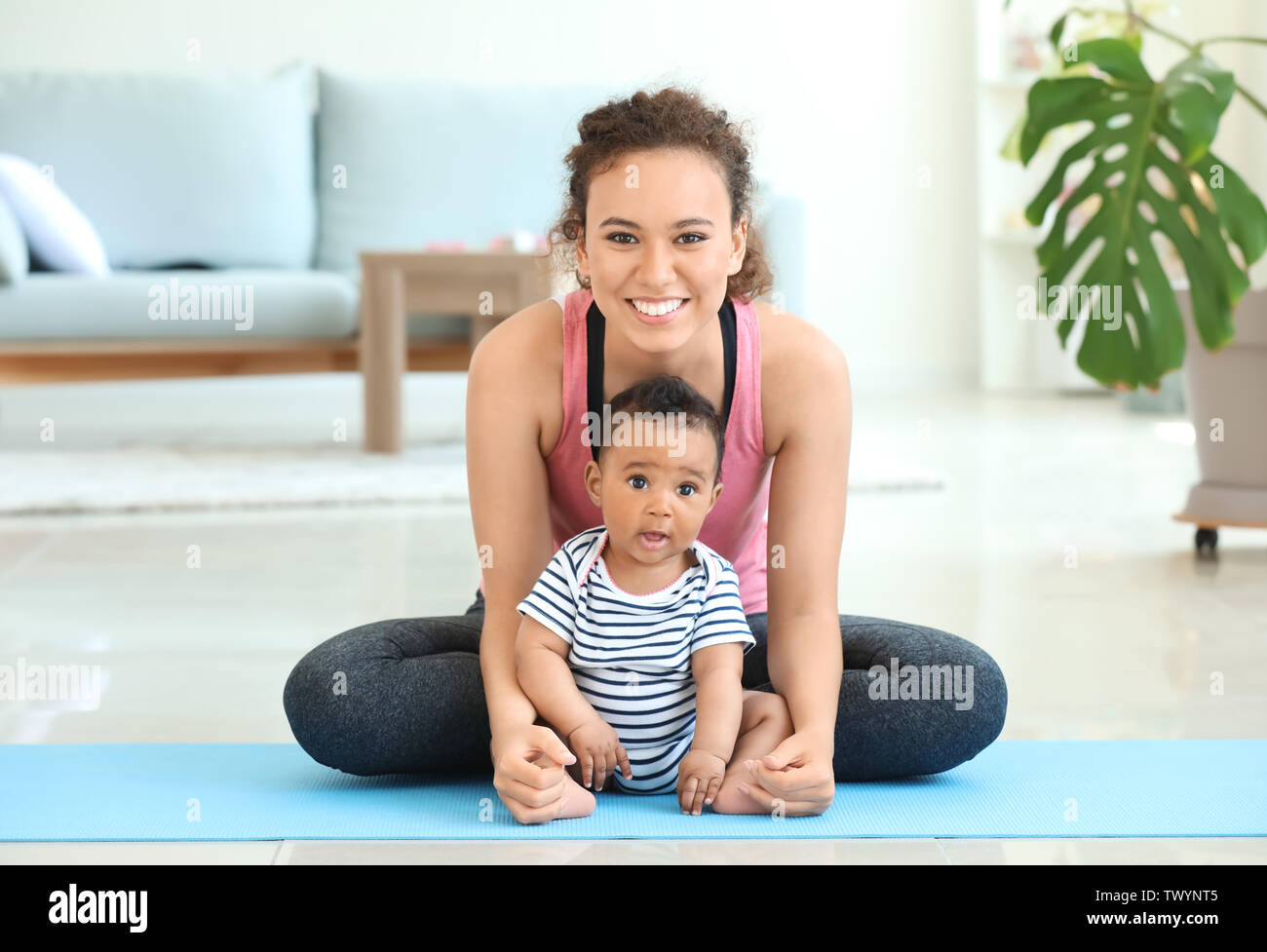 African-American mother training with cute little baby at home - Stock Image